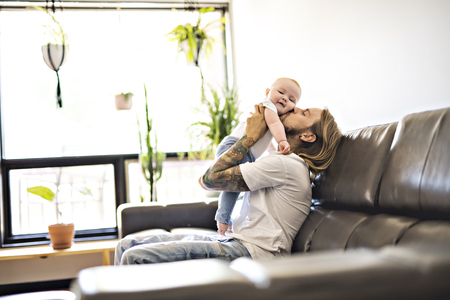 father playing with baby daughter on sofa at home
