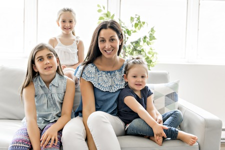 Happy young woman with children on sofa at home 免版税图像