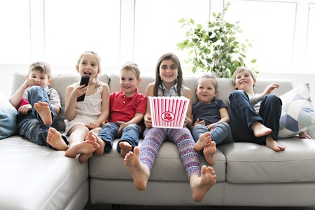child group eating popcorn together on sofa