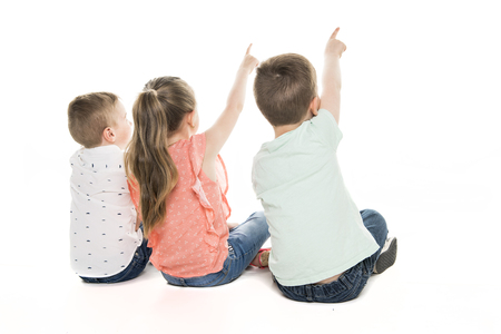 Back view of child group sitting on floor looking at wall