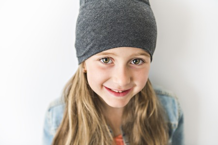 Portrait of a little girl. Studio photography of girl have toque on head