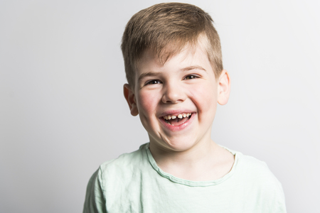 five year old boy posing over white studio background