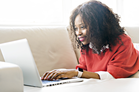 Attractive black young woman using a laptop while relaxing on a sofa at home
