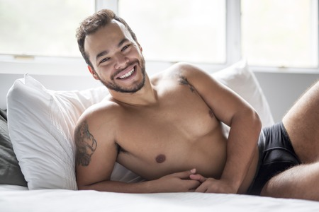 A young mexican man shirtless in white bed