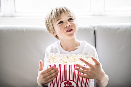 adorable child Watching TV in his home with popcorn