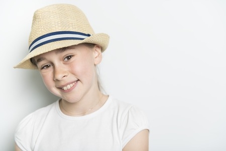 Portrait of cute, confident 9 years old girl, isolated on white with hat Stock fotó