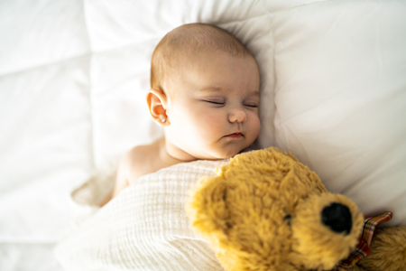 A 4 month baby sleeping on a white bed at home with bear