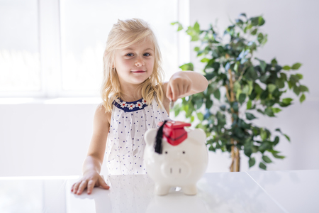 smiling little girl with piggy bank and money at home 스톡 콘텐츠