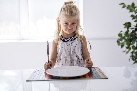 Furious little girl waiting for dinner. Holding a fork in the hand