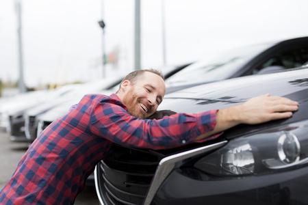 Ein glücklicher junger Mann, der sein Auto außerhalb des Garagenladens umarmt