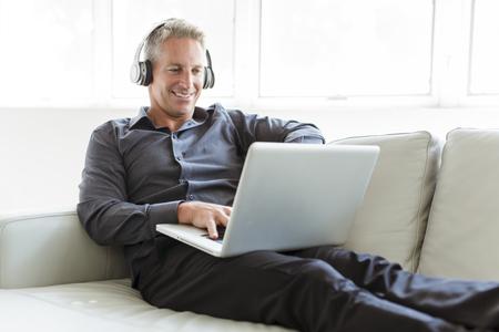 Portrait of happy mature man using laptop lying on sofa in house Standard-Bild