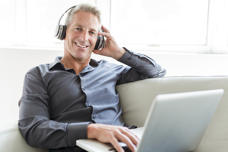 Portrait of happy mature man using laptop lying on sofa in house 版權商用圖片