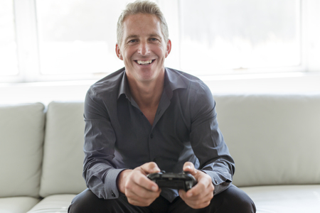 Portrait of single 40s man sitting in sofa play video game
