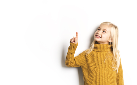 A Cute girl 5 year old posing in studio pointing