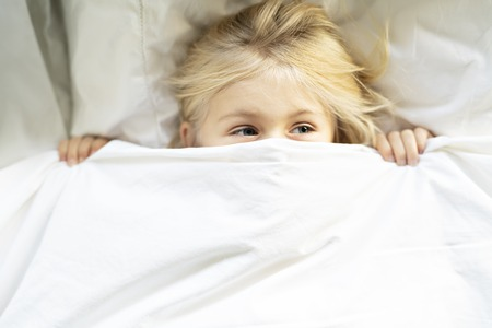 A little girl in bed below the covers