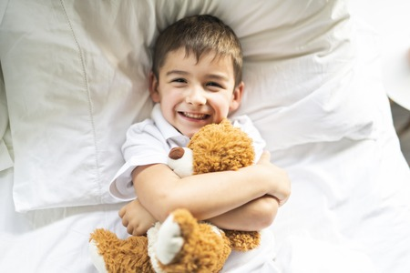 A Child lying in bed with a plush teddy bear Stock fotó