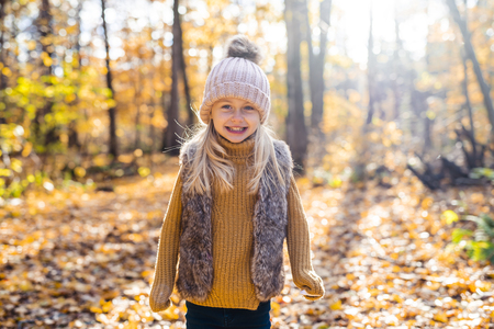An Autumn portrait of cute blond child girl