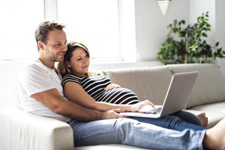 Een stel met een zwangere vrouw die samen een laptopcomputer gebruikt
