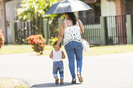 A mother and son walking on street with umbrella on a sunny day