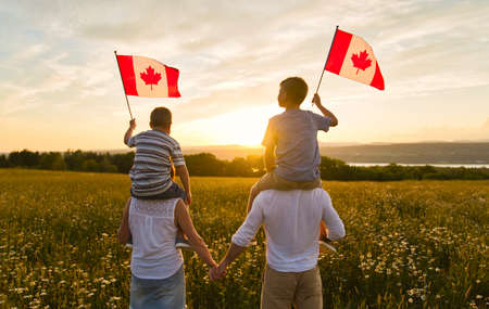 Adorable cute happy Caucasian boys holding Canadian flag on the father shoulder