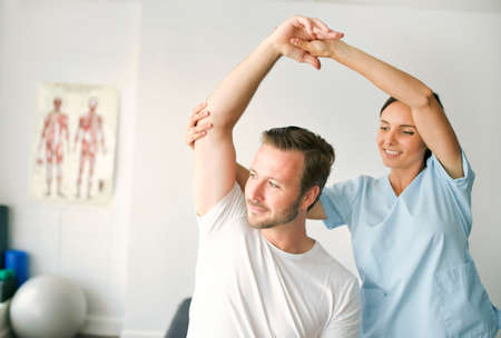physiotherapist doing treatment with patient in bright office Standard-Bild