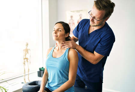 Male Physical Therapist Stretching a Female Patient nack Imagens