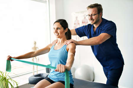 Male Physical Therapist Stretching a Female Patient Slowly. Stock Photo