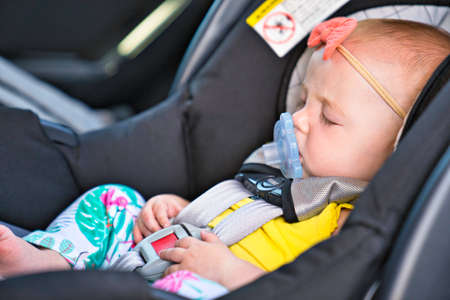Little baby sleeping in a car in a child car seat