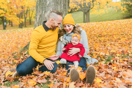Baby daughter and her parents in the autumn season in park