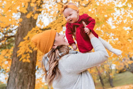 Baby daughter and her mother in the autumn season in park
