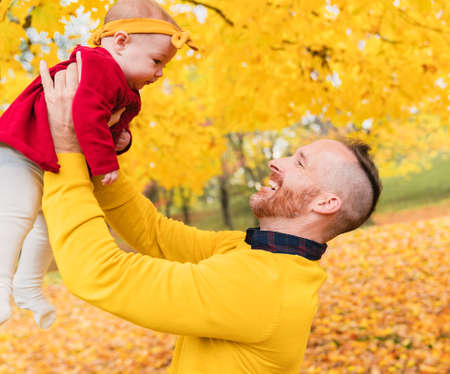 Baby daughter and her father in the autumn season in park 版權商用圖片