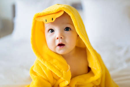 Baby wearing yellow bathrobe duck on parents bed after bath 版權商用圖片 - 157977205