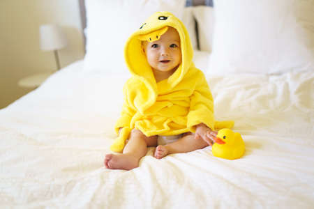Baby wearing yellow bathrobe duck on parents bed after bath