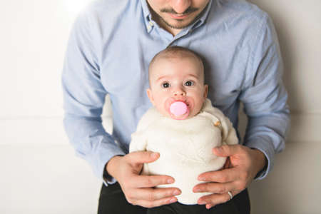 Young daddy with his daughter sit on a white floor studio, trying to consoling