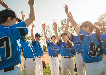 Group of baseball players standing together on the playground with hand celebration