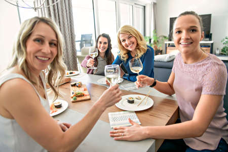 Group of attractive mature people eating sushi at home Standard-Bild