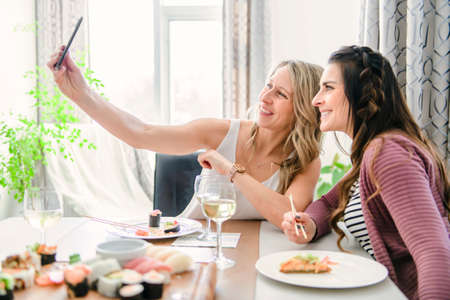 Two attractive mature people eating sushi at home taking photo Stock Photo