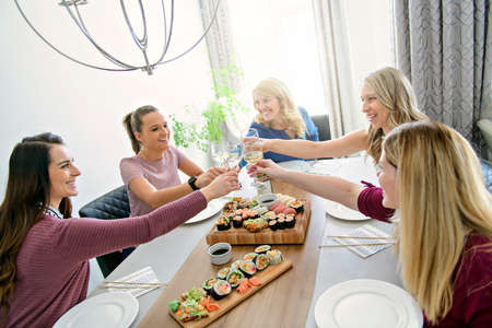 Group of attractive mature people eating sushi at home Stock Photo