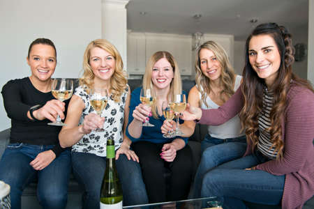 Five mature women toast and celebrating their meeting on the sofa