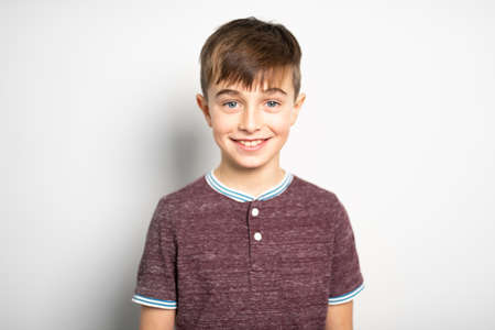 A portrait of young boy over white wall
