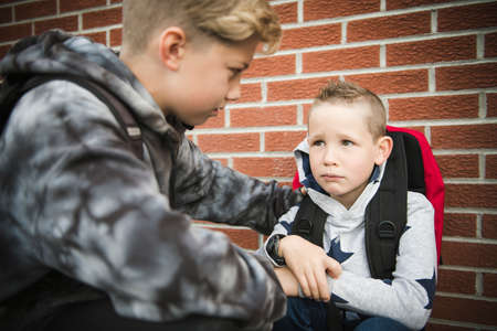 boy problem at school, sitting and consoling child each other