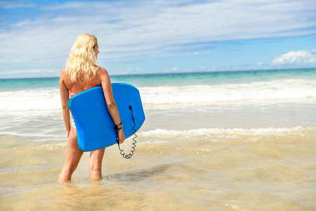 A Body Boarder woman holding the board with wave on the back