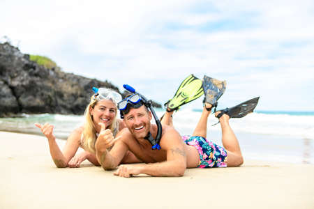 Couple lay on the beach is going to swim and snorkle on hawaii beach Stock Photo