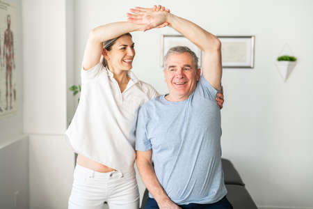 A Modern rehabilitation physiotherapy worker with senior client Stock Photo