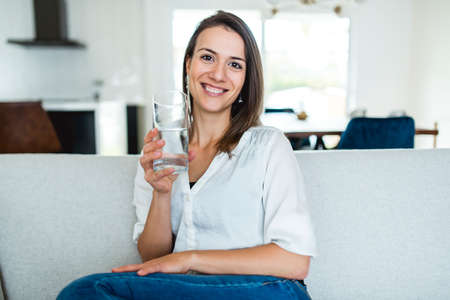 Brunette having good time on the living room with water glass