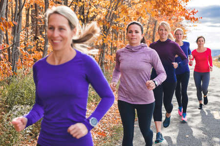 woman group out running together in an autumn park they run a race or train in a healthy outdoors lifestyle concept