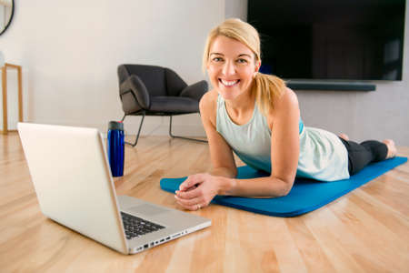 Portrait of fit woman training in her living room with laptop