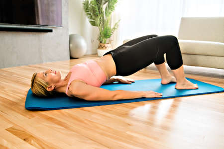 Portrait of fit woman training in her living room on an exercise mat