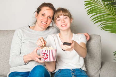 A Portrait of a woman and daughter watching TV while eating popcorn on the sofa
