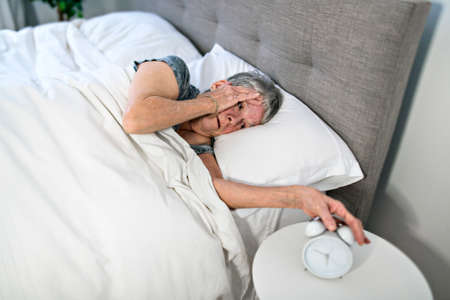 A Senior woman having sleep disorder, lying in bed